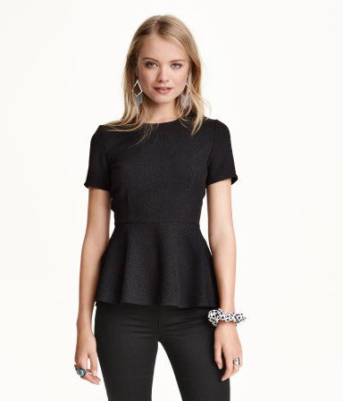 Black, short-sleeved, textured peplum top in a stretchy woven .